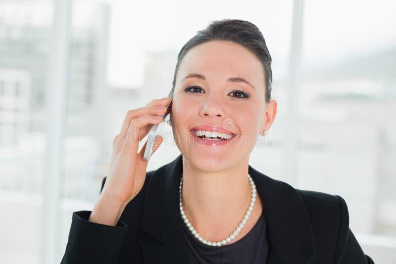 关闭使用手机的一名微笑的典雅的女实业家 免版税库存照片