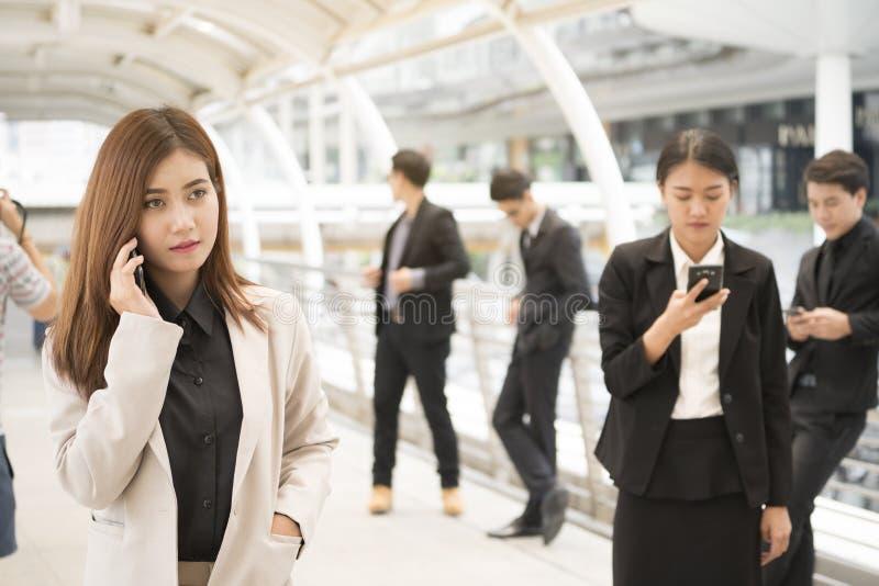 关闭使用智能手机的商人和女实业家 免版税库存照片