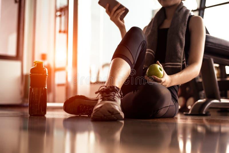关闭使用智能手机的妇女和拿着苹果,当锻炼在健身健身房时 体育和技术概念 生活方式和 免版税库存图片