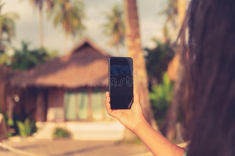 关闭使用有屏幕的照片妇女流动巧妙的电话为拷贝空间:概念观看的网站,付款服务,预定的旅馆 库存图片