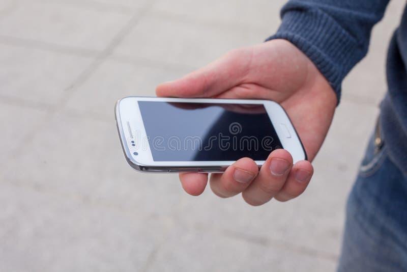 关闭使用流动巧妙的电话的一个人室外 库存图片
