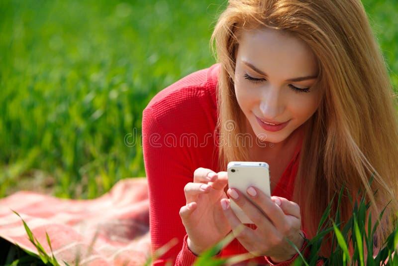 关闭使用流动巧妙的电话的妇女在公园 免版税库存图片