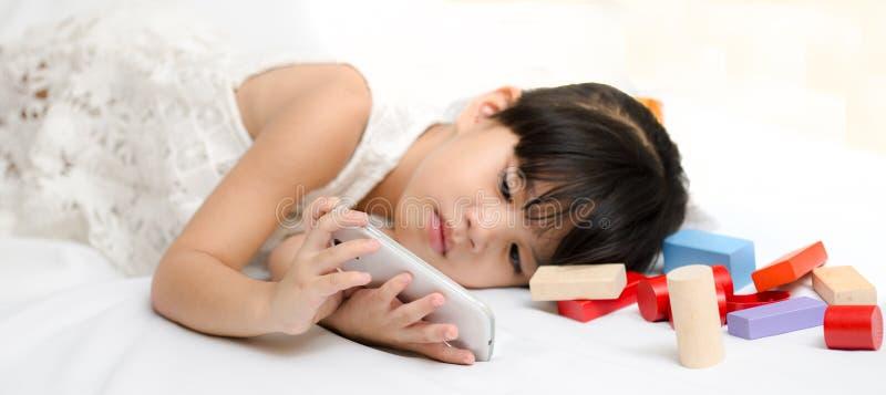 关闭使用流动巧妙的电话的手孩子 免版税库存照片