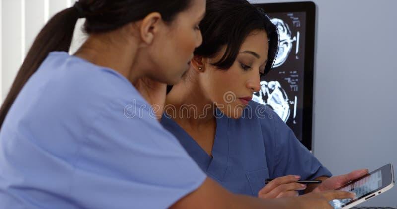 关闭使用片剂和手机的两位医生 图库摄影