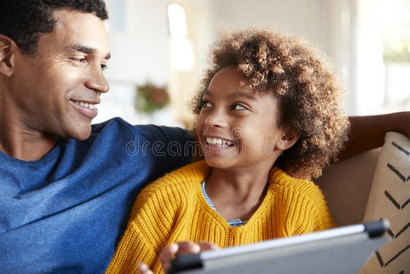 关闭使用片剂计算机的父亲和女儿,看彼此微笑,选择聚焦 免版税库存图片