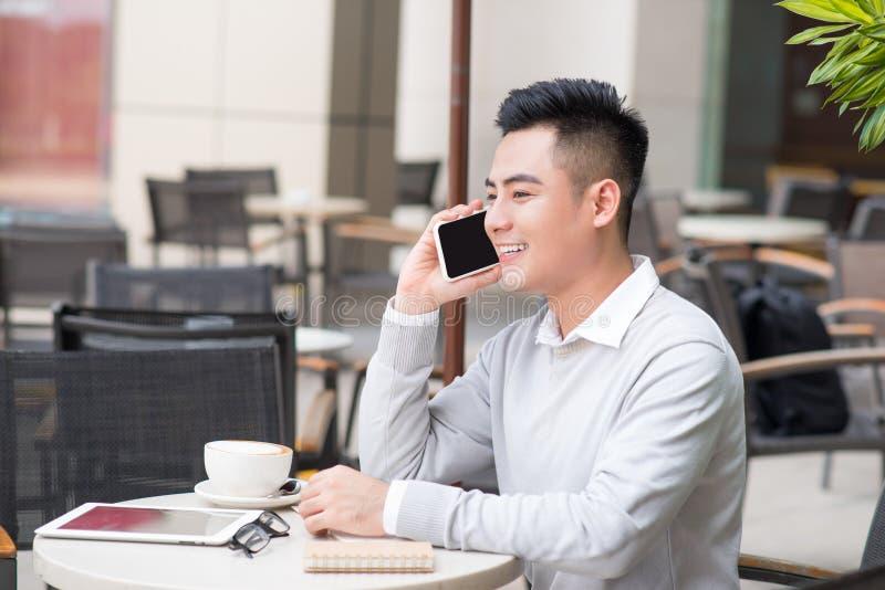 关闭使用电话神色的年轻人窗口 或者商人联络顾客 免版税库存图片