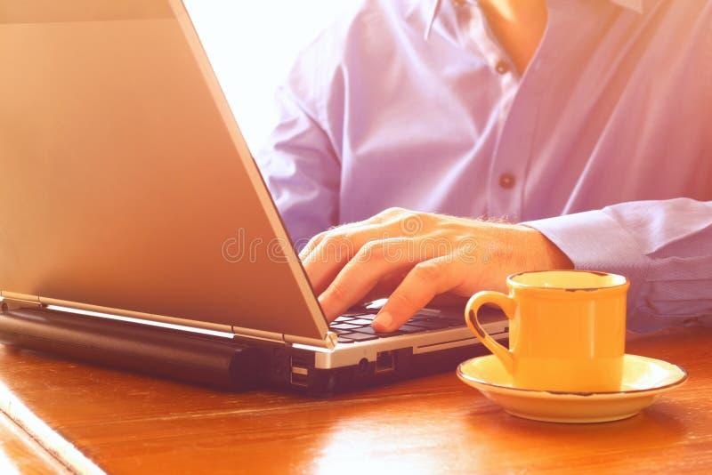 关闭使用膝上型计算机的人的图象在咖啡旁边 棒图象夫人减速火箭的抽烟的样式 选择聚焦 库存图片