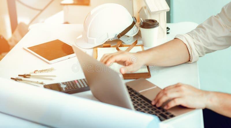 关闭使用膝上型计算机的土木工程师画象对计划PR 免版税库存图片