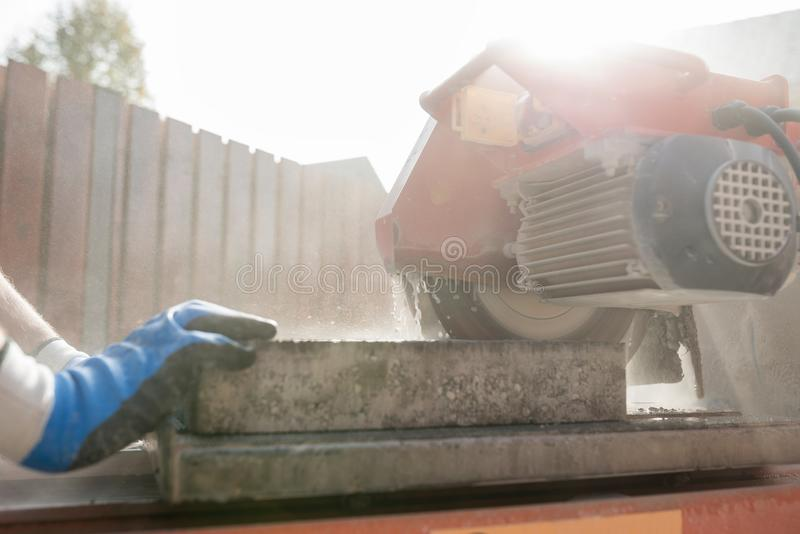 关闭使用角度研磨机的建筑承包商的看法或 库存照片
