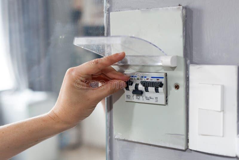 关闭保险丝箱子的妇女手在房子里 免版税库存图片