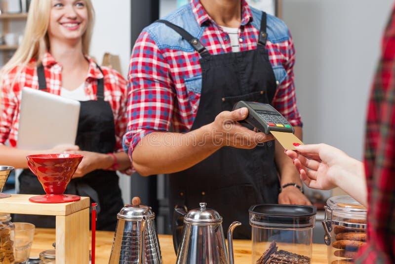 关闭信用卡支付咖啡店酒吧柜台barista服务客户 免版税库存图片