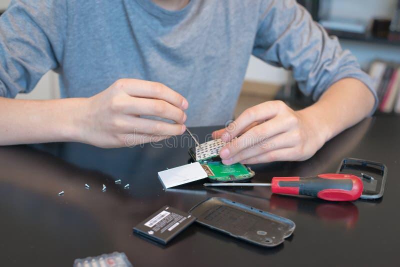 关闭修理一个手机的手 免版税库存照片