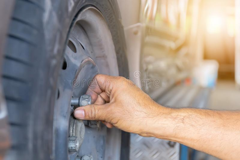 关闭修理技工手在维护期间松开汽车轮子坚果改变的轮胎  免版税库存图片