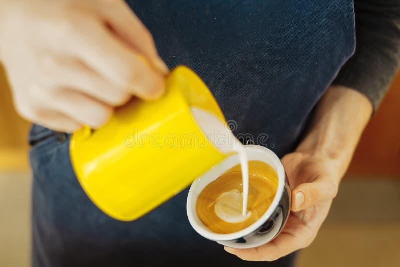 关闭倒蒸的牛奶的barista入做拿铁艺术的咖啡杯 库存照片