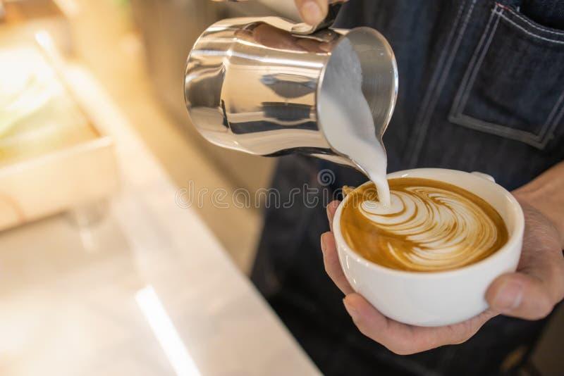 关闭倒stremed牛奶的barista手入白色杯子热的咖啡创造拿铁艺术 图库摄影