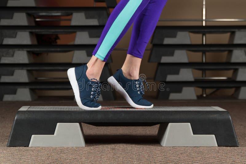 关闭做在步平台的妇女佩带的白色运动鞋脚趾轻拍在有氧 库存图片