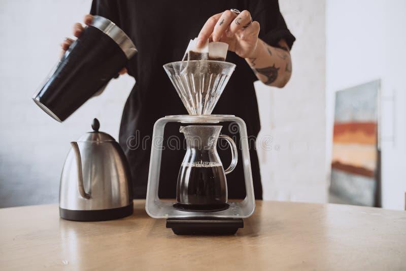 关闭做手煮的咖啡的barista 免版税库存照片