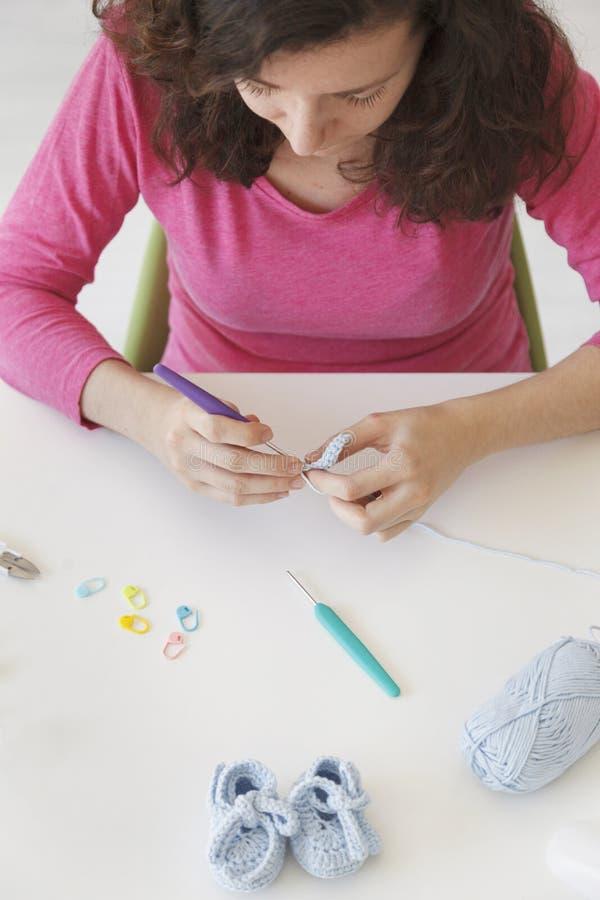 关闭做自创钩编编织物与needl的妇女手 库存图片