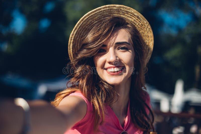 关闭做selfie的帽子的画象尼斯笑的女孩在海滩 秀丽深色的妇女havin逗人喜爱的夏天时尚画象  免版税库存图片