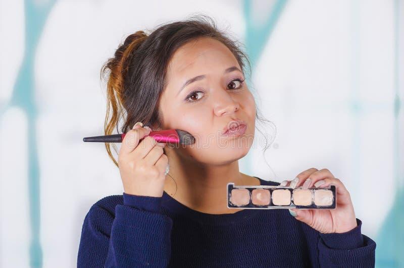 关闭停滞制造调色板和做在她的面孔的年轻美丽的妇女疯狂的构成使用一把刷子,在a 免版税库存图片