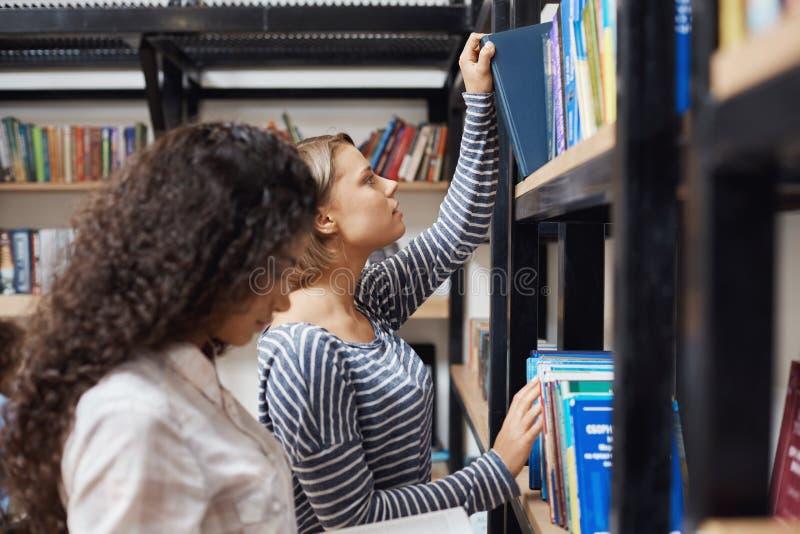 关闭停留近的书架的镶边衬衣的年轻悦目白肤金发的女孩在现代图书馆里,去采取a 免版税库存照片