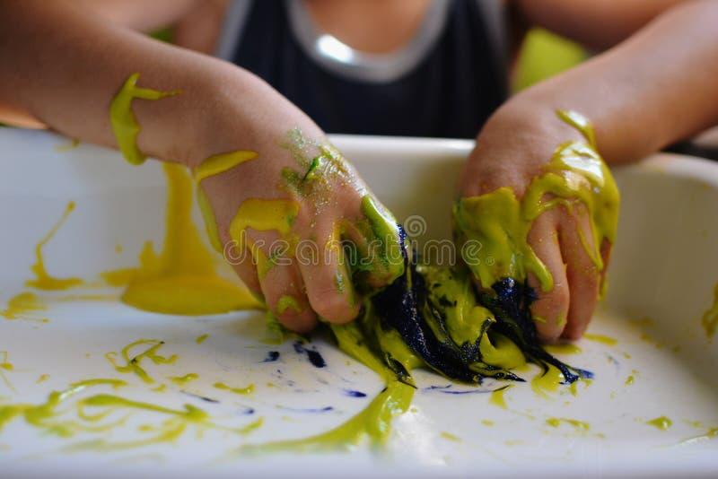 关闭儿童使用与手工制造太空星群的软泥的` S手 免版税库存图片