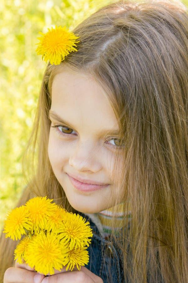 关闭八岁的女孩画象用蒲公英在手上 免版税库存图片
