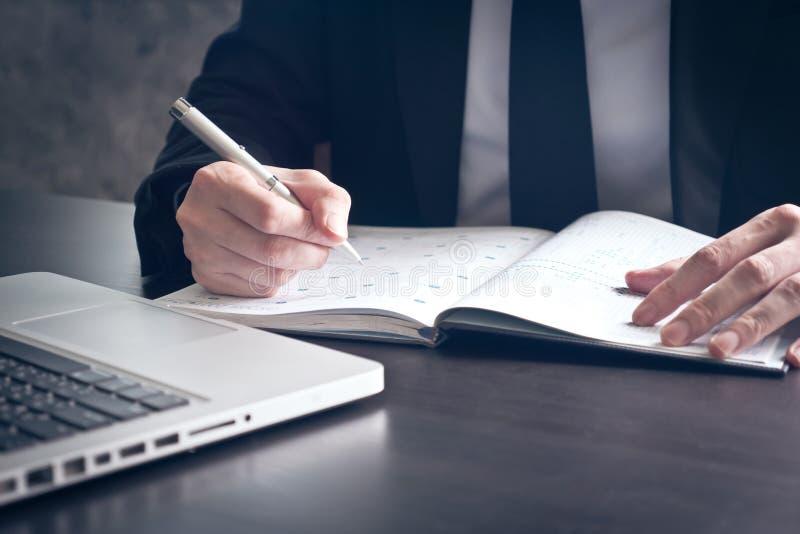 关闭写一些数据的商人在笔记本在办公桌 免版税图库摄影