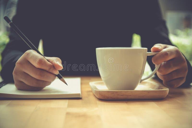 关闭写在有铅笔的笔记本的妇女手,举行co 免版税库存图片