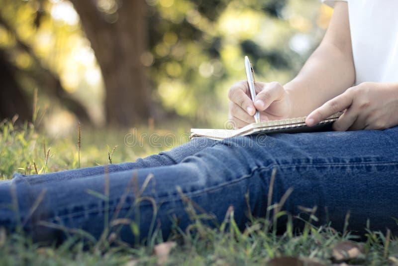 关闭写在笔记本的少妇在公园,在edu的概念 免版税库存照片