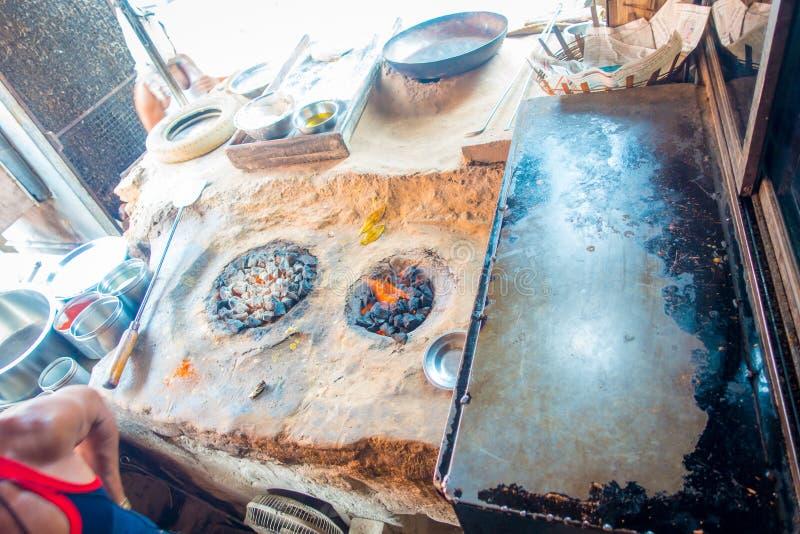 关闭准备在一个金属盘子的印地安食物,在旁边在地板的白炽岩石在斋浦尔,印度 免版税库存照片