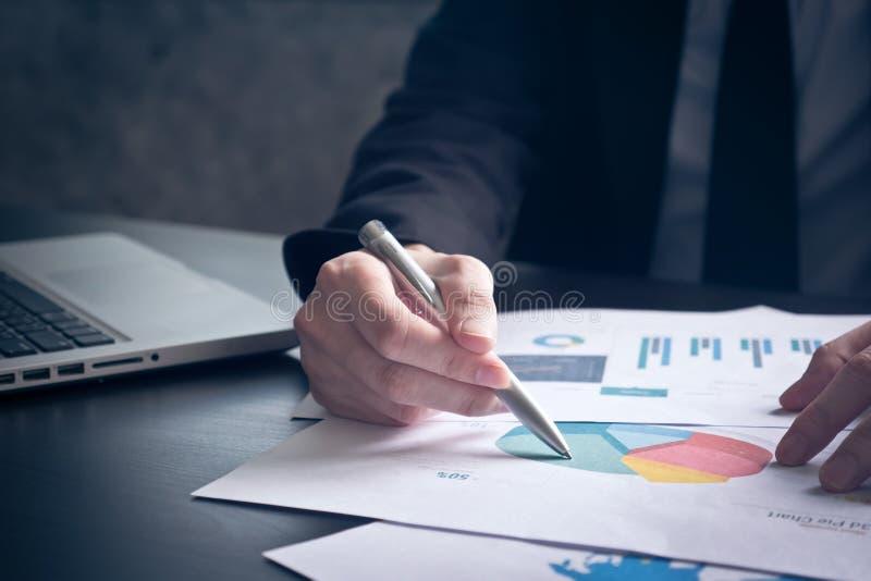 关闭分析在书桌上的商人投资图 免版税库存照片