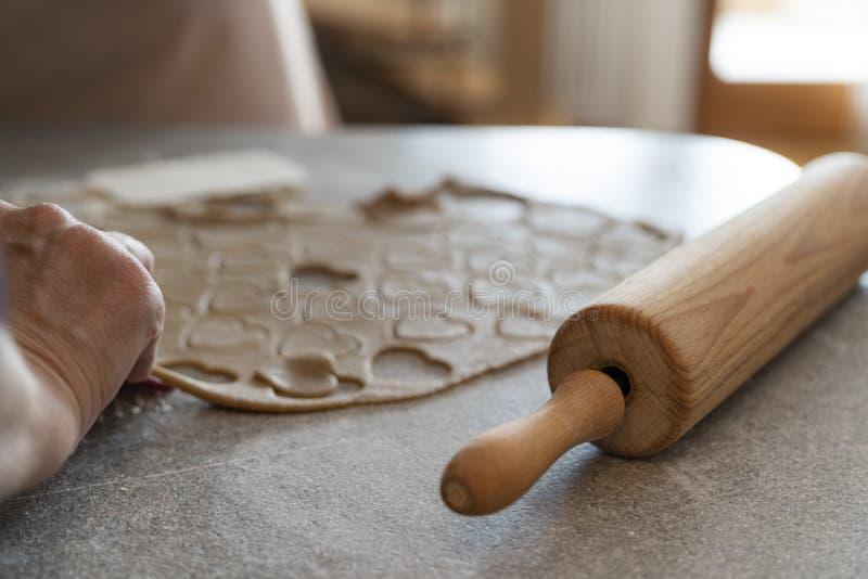 关闭删去饼干面团的曲奇饼的一根滚针和手 免版税库存图片