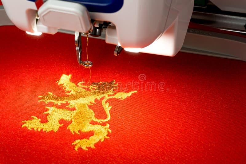 关闭刺绣机器和金在红色织品的狮子商标的图片 库存照片
