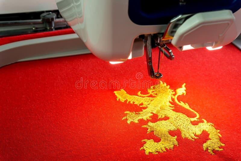 关闭刺绣机器和金狮子设计的图片 库存照片