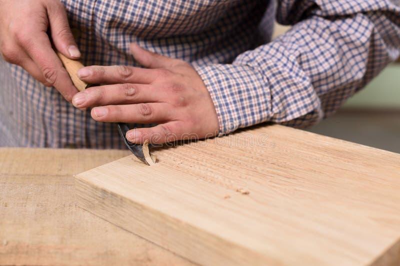 关闭削减有凿子的木匠手木板 库存照片
