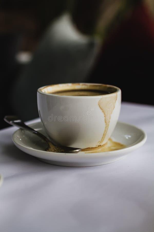 关闭加奶咖啡在茶碟溢出的杯子浓咖啡 库存图片