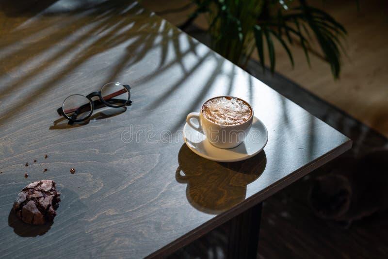 关闭加奶咖啡杯子、燕麦曲奇饼和玻璃在黑暗的木桌上 免版税库存照片