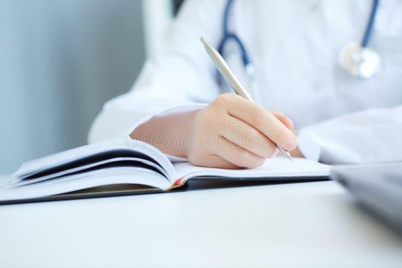 关闭医生采取笔记的` s手 保护回合、耐心参观检查、医疗演算和统计概念 免版税库存照片