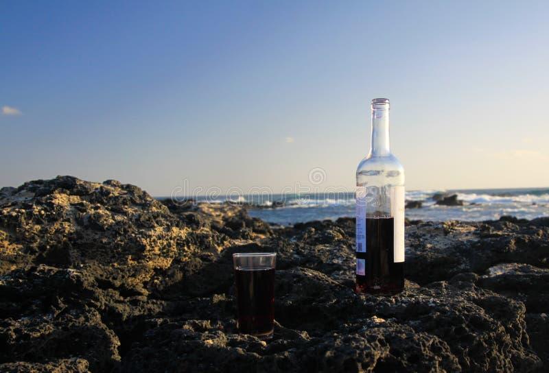 关闭半满的红酒酒瓶和玻璃在海滩岩石有海浪背景- El Cotillo, 免版税库存图片