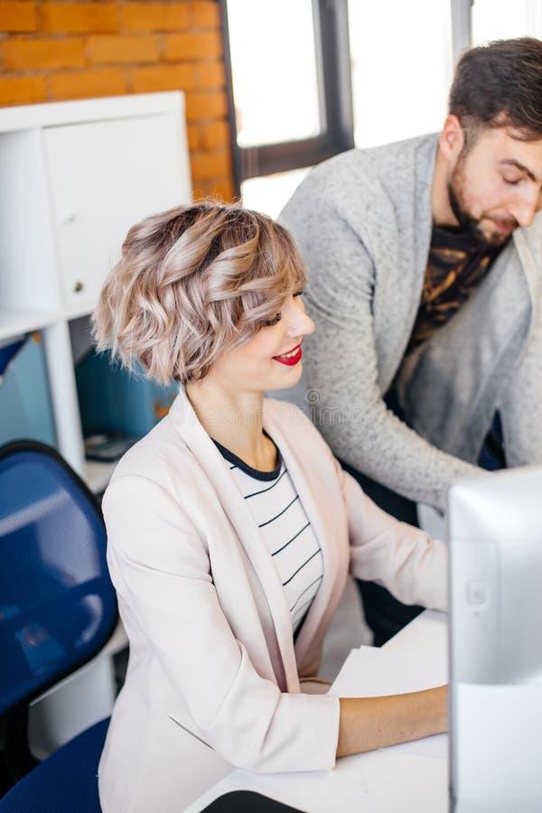 关闭华美的微笑的女性开会播种的照片在办公室桌上 免版税库存图片