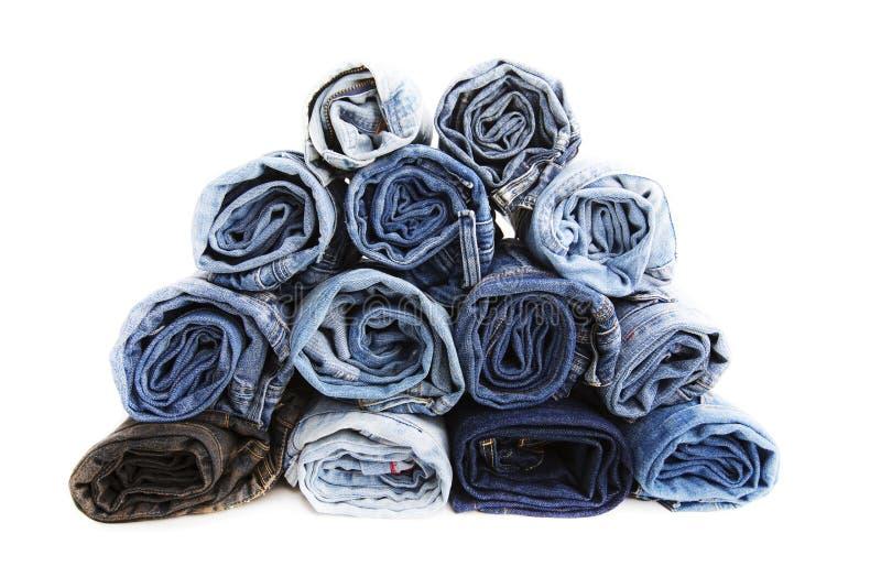 关闭卷起了蓝色牛仔裤裤子,显示纹理的深蓝牛仔布长裤 库存图片