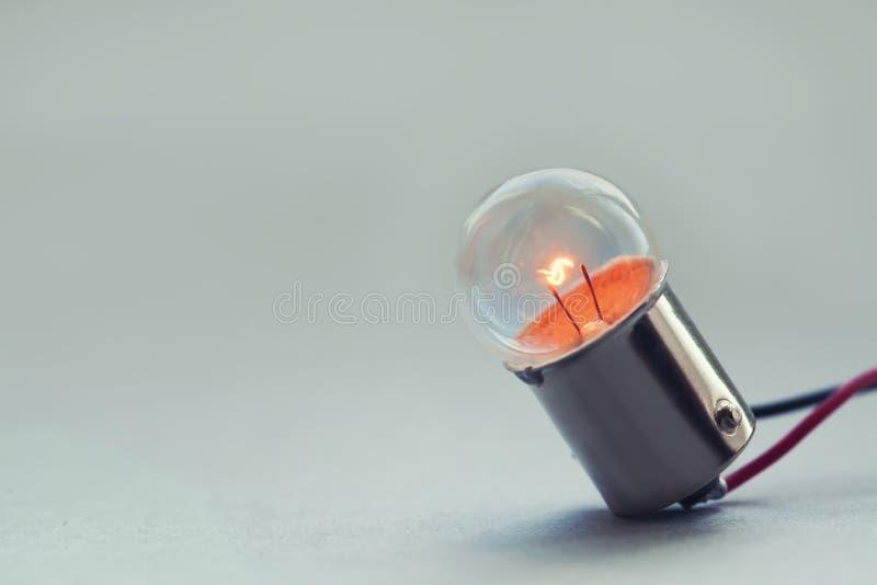 关闭发光的电灯泡,减速火箭的样式白炽灯宏指令视图 背景给颜色穿衣折叠了橙红温暖的黄色 软绵绵地集中 复制空间 库存图片