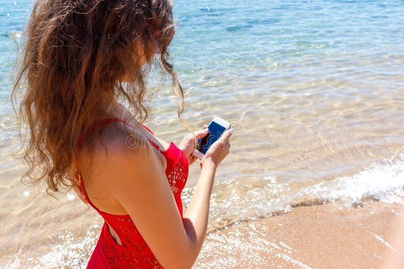 关闭发短信在海滩的一个巧妙的电话的妇女 海运在背景中 库存照片