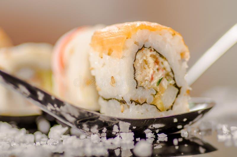 关闭可口选择聚焦在黑色寿司卷有服务的小盐的一把金属匙子 免版税库存图片