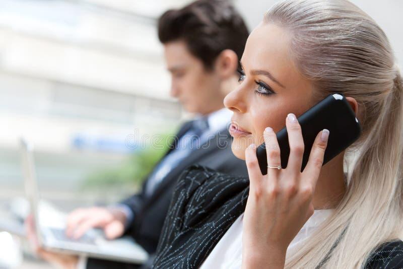 女实业家谈话在巧妙的电话在会议上。 库存照片