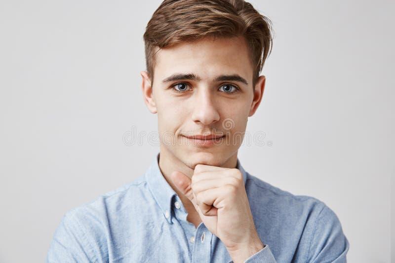 关闭可爱的年轻人画象  请,谈话,我听着 英俊的年轻人听见他的问题 免版税库存照片