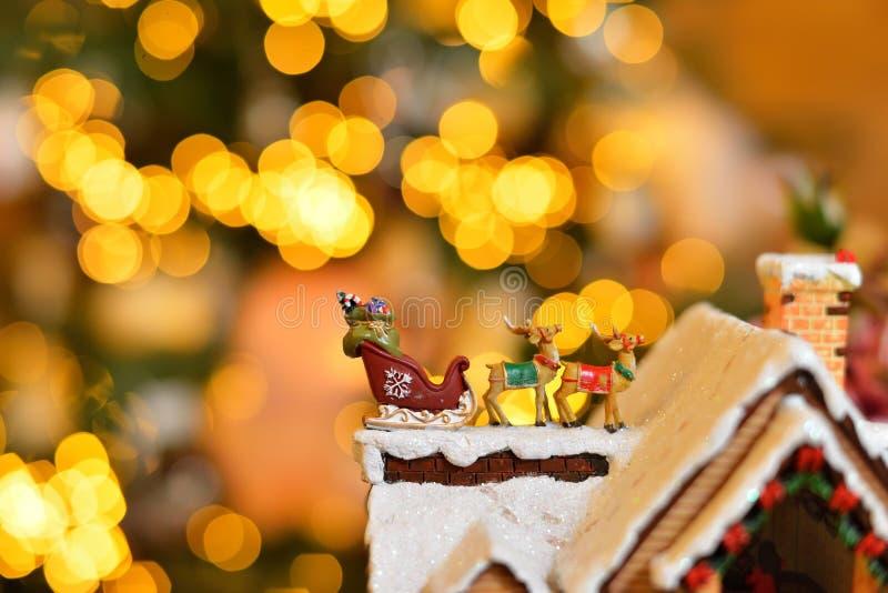 关闭可爱的驯鹿和圣诞老人雪橇与礼物圣诞节装饰的 显示在bokeh点燃背景 库存照片