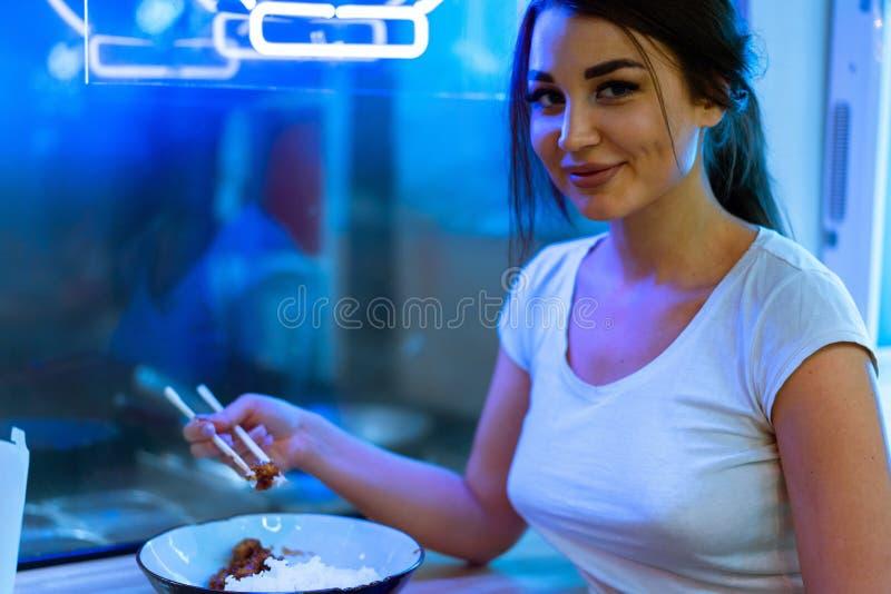 关闭吃与筷子的年轻可爱的妇女亚洲食物在咖啡馆 库存照片