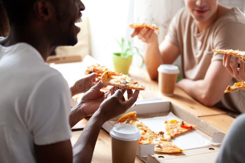 关闭吃比萨的不同的朋友的播种的图象 库存照片